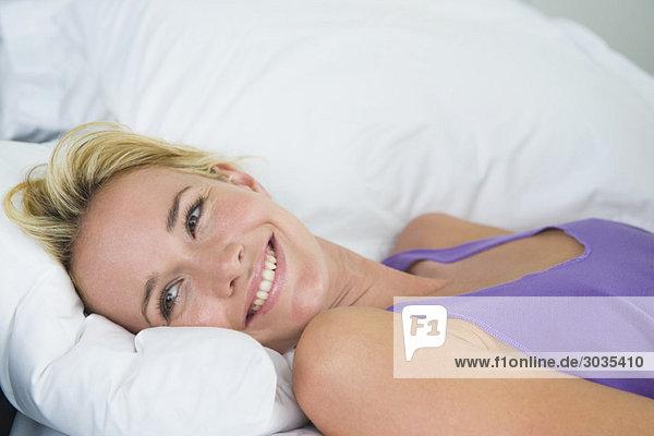 Frau auf dem Bett liegend und lächelnd