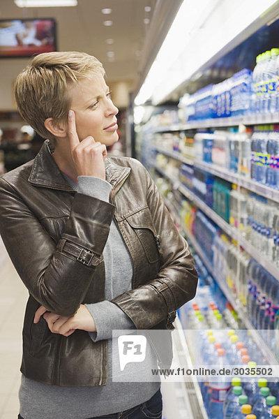 Frau denkt daran  eine Wasserflasche im Laden zu kaufen.