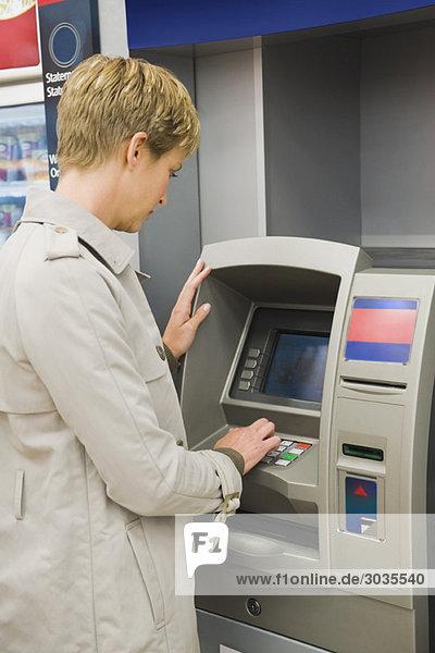 Frau  die PIN-Nummer in einem Geldautomaten eingibt