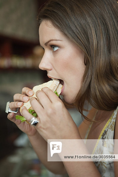 Woman eating sandwich in a cafe