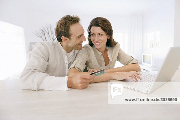 Couple holding a credit card and working on a laptop