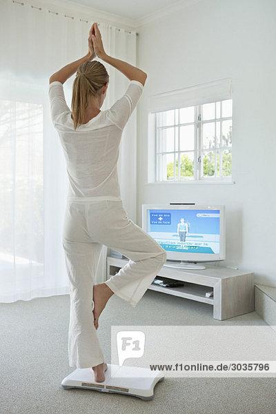 Frau beim Yoga vor dem Fernseher