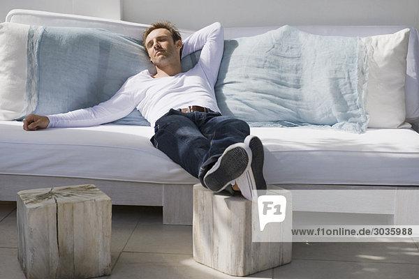 Mann auf einer Couch liegend
