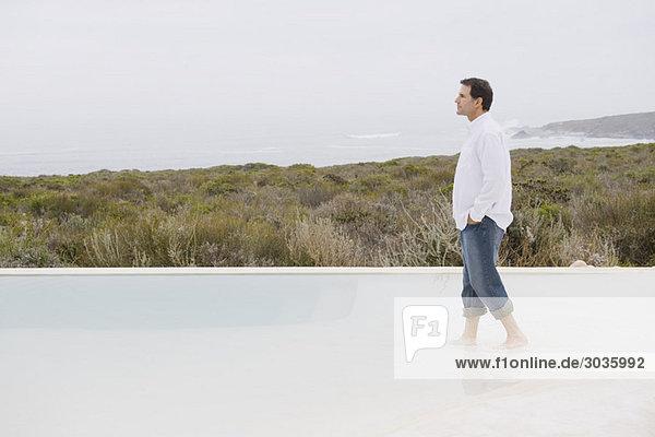 Ein Mann  der in einem Unendlichkeitsbecken spazieren geht.