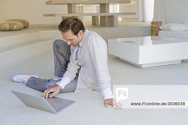Mann sitzt auf dem Boden und arbeitet am Laptop