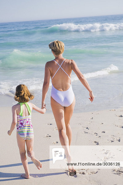 Frau  die mit ihrer Tochter am Strand rennt