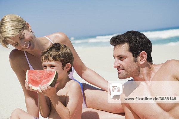 Junge isst eine Wassermelone mit seinen Eltern am Strand.