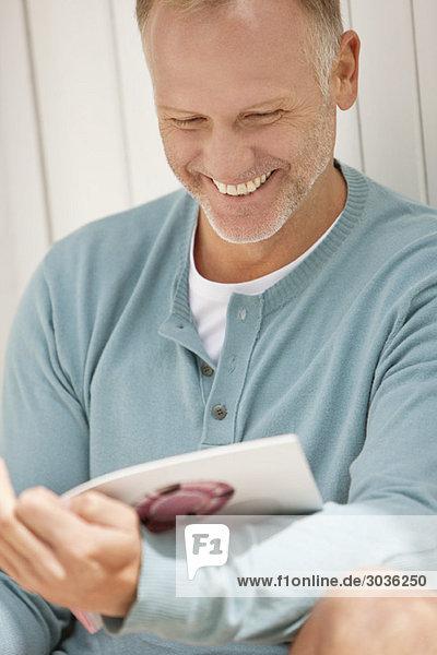 Mann liest eine Zeitschrift und lächelt