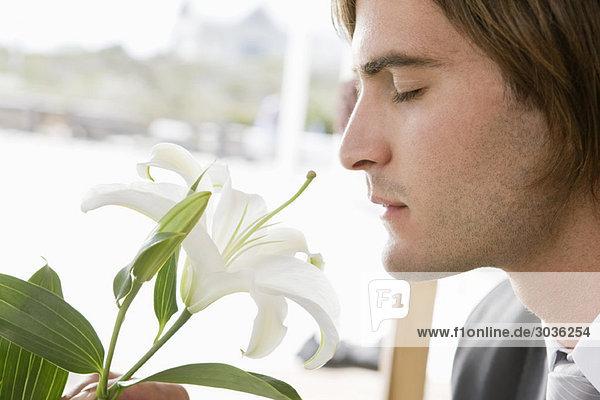 Nahaufnahme eines Bräutigams  der eine Lilienblüte riecht.