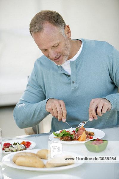 Mann beim Frühstück am Esstisch