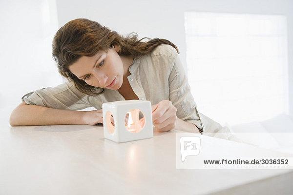 Frau zündet eine Kerze an