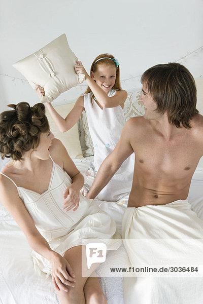 Ein Paar spielt mit seiner Tochter auf dem Bett.
