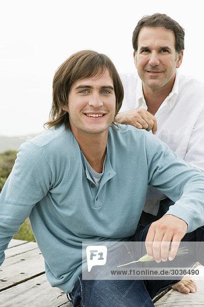 Zwei Männer sitzen auf einer Promenade.