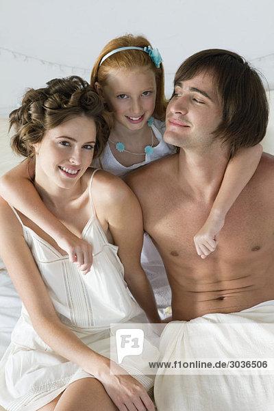 Ein Paar lächelt mit seiner Tochter auf dem Bett.