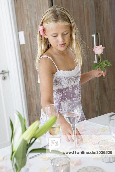 Mädchen  das eine Blume hält und an einem Esstisch steht.