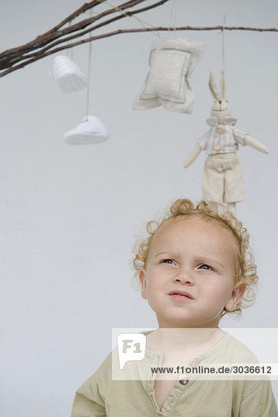 Nahaufnahme eines kleinen Jungen mit Spielzeug  das an Stöcken über ihm hängt.