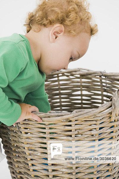 Baby Junge schaut in einen Weidenkorb