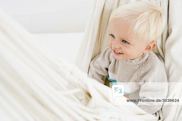 Baby Junge sitzt in einer Hängematte
