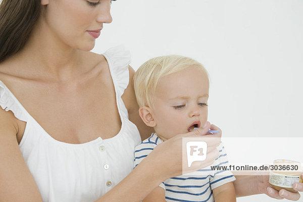 Frau füttert ihren Sohn mit Honig