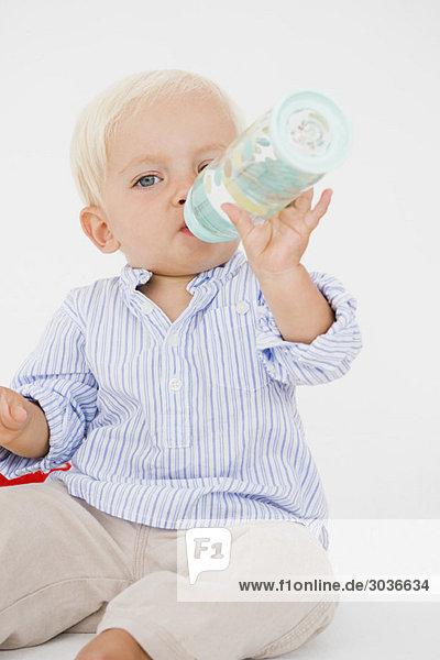 Babyboy trinkt Wasser aus einer Babyflasche