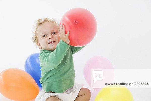 Baby Junge spielt mit Luftballons