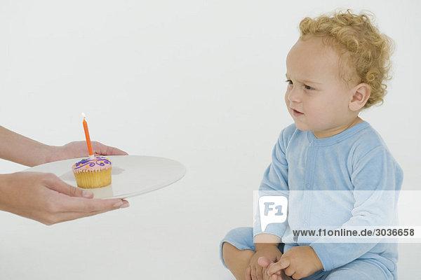 Frau bietet ihrem Sohn an seinem ersten Geburtstag einen Muffin an.