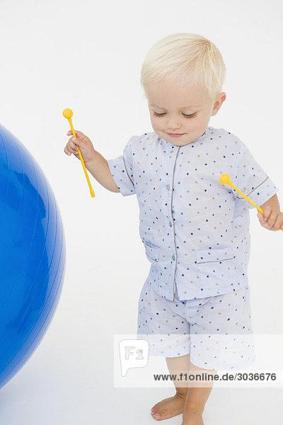 Junge hält Xylophonschlägel und steht neben einem Fitnessball.