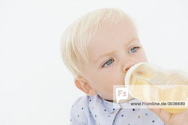 Baby Junge trinkt Saft aus einer Babyflasche