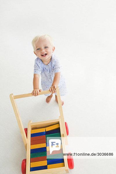Baby Junge schiebt einen Wagen