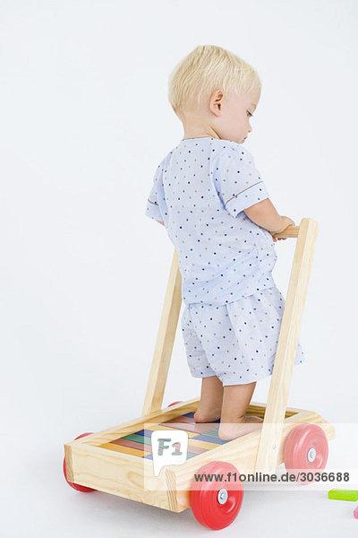 Kleiner Junge spielt mit einem Schubkarren
