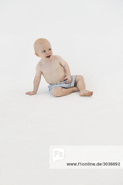 Junge sitzt auf dem Boden und lächelt.
