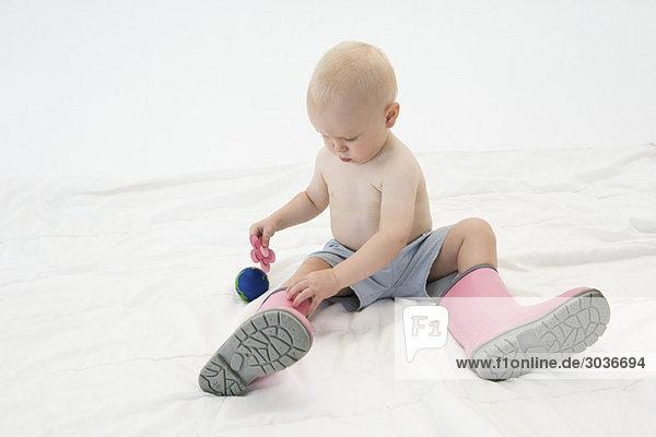 Baby Junge mit Gummistiefeln