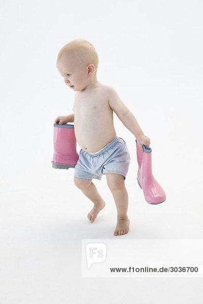 Junge trägt ein Paar Gummistiefel.