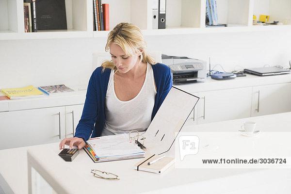 Geschäftsfrau mit Taschenrechner