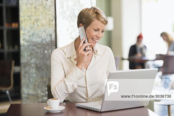 Geschäftsfrau spricht auf dem Handy und schaut sich einen Laptop an.