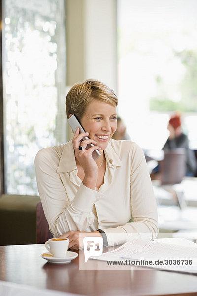 Geschäftsfrau sitzt in einem Restaurant und redet auf dem Handy