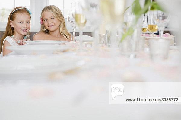 Zwei Mädchen sitzen am Esstisch