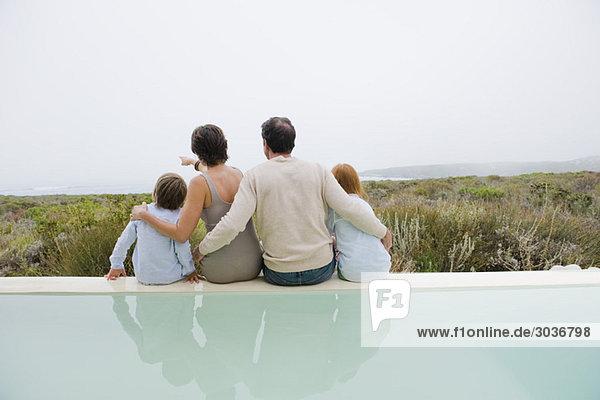 Familie am Pool sitzend