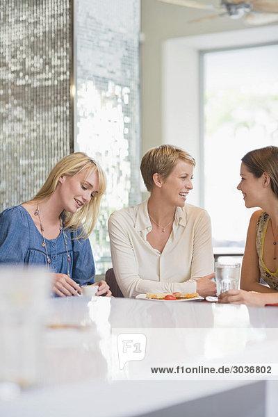 Drei Frauen sitzen in einem Restaurant.