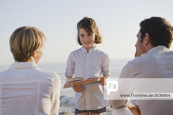 Mädchen beim Lesen eines Buches vor ihren Eltern