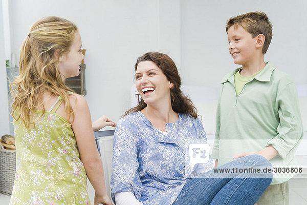 Frau lächelt mit ihren Kindern