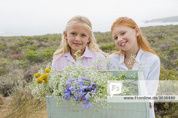 Zwei Mädchen  die eine Schachtel mit Blumen tragen und lächeln.