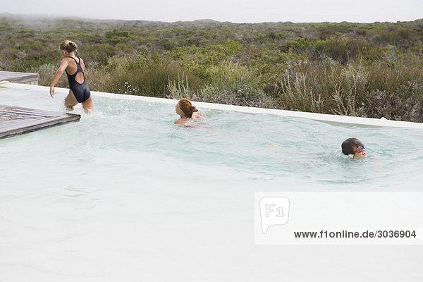 Zwei Mädchen schwimmen in einem Infinity-Pool mit einem Jungen.