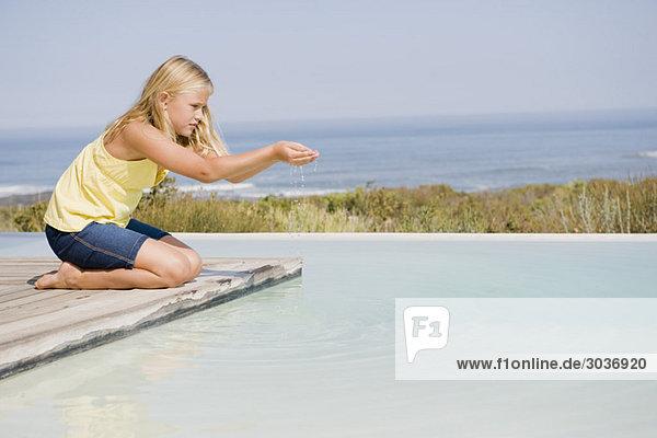 Mädchen  die auf einer Plattform an einem Infinity-Pool spielen.
