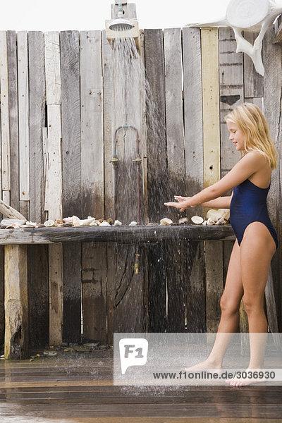 Mädchen unter einer Stranddusche