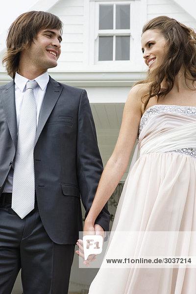 Jungvermähltes Paar lächelt sich an.