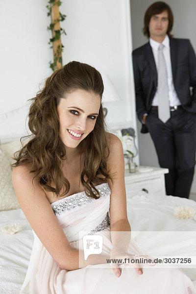 Die Braut sitzt auf dem Bett und der Bräutigam steht hinter ihr.