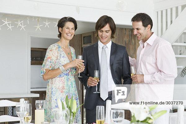 Mann trinkt Champagner mit seinen Eltern