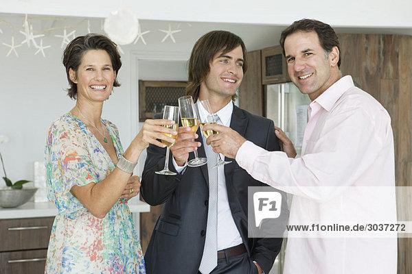Mann und seine Eltern stoßen mit Champagner an.