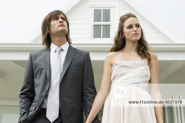 Frischvermähltes Paar vor einem Haus